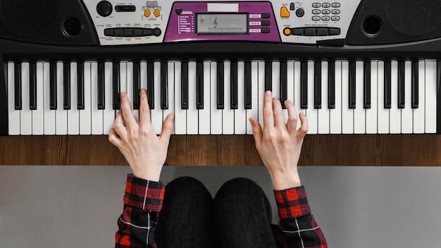 Widok z góry ręce grające na pianinie cyfrowym