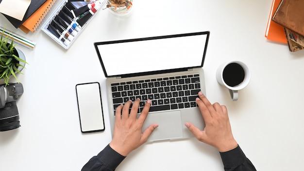 Widok z góry ręce kreatywnego mężczyzny piszącego na komputerze laptop z białym pustym ekranem, który stawia na białym stole roboczym otoczonym filiżanką kawy, pustym ekranem smartfona i akcesoriami.