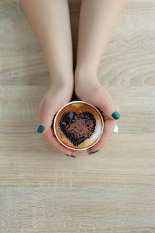 Widok z góry ręce trzymając białą filiżankę kawy. wydruk serca na kawie