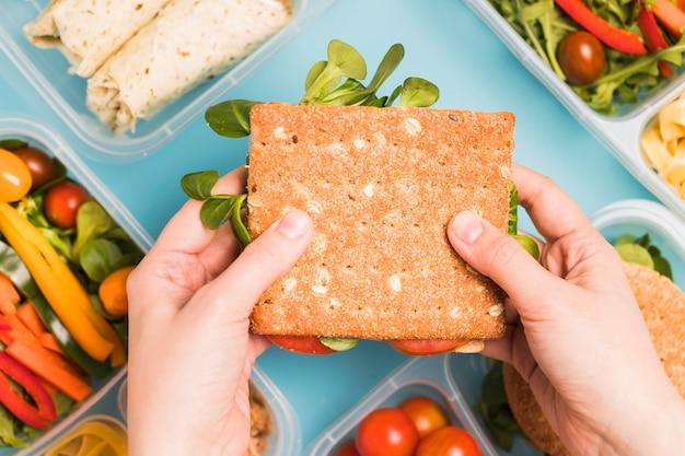 Widok z góry ręce trzymając kanapkę krakersa