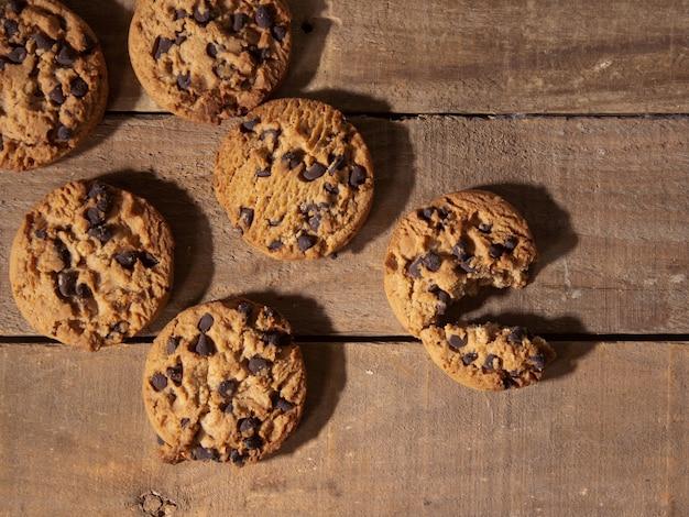 Widok z góry ręcznie robionych ciasteczek z kawałkami czekolady na antycznym ciemnym tle drewna