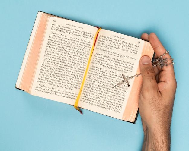 Widok z góry ręka trzyma świętą księgę i naszyjnik