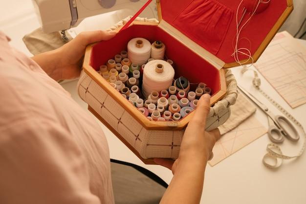Widok z góry ręka trzyma szpule nici, szycie i szycie koncepcja produkcji
