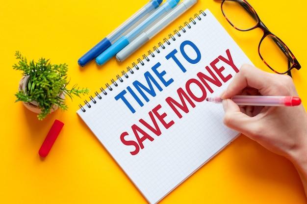 Widok z góry, ręka trzymająca ołówek pisanie lista czas oszczędzać pieniądze z notatnikiem, długopisem, okularami, kalkulatorem i zielonym kwiatkiem na żółtym stole. koncepcja biznesu i edukacji