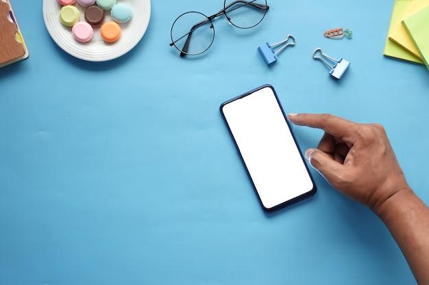 Widok z góry ręki człowieka za pomocą inteligentnego telefonu na biurku.