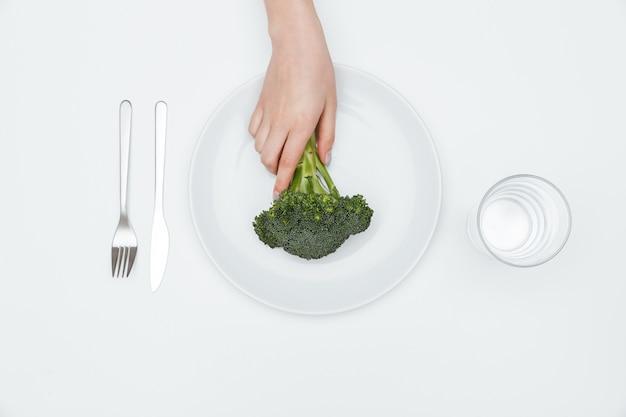 Widok z góry ręki kobiety biorącej brokuły z talerza