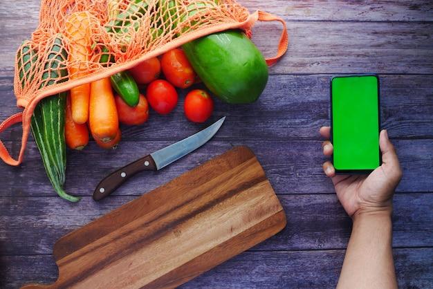 Widok z góry ręki mans trzymającej inteligentny telefon ze świeżymi warzywami na stole