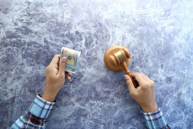 Widok z góry ręki osoby uderzającej młotkiem i trzymającej gotówkę