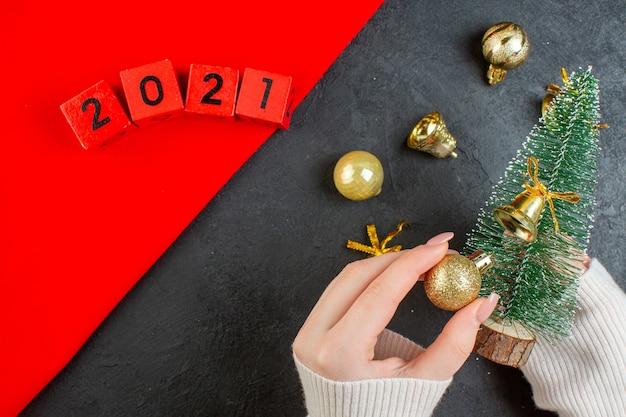 Widok z góry ręki trzymającej choinkę i akcesoria do dekoracji z numerami na ciemnym stole