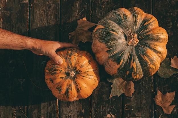 Widok z góry ręki trzymającej dynię z jesiennego drewnianego stołu z liśćmi