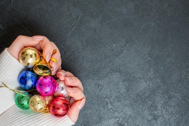 Widok z góry ręki trzymającej kolorowe akcesoria do dekoracji po prawej stronie na ciemnym tle