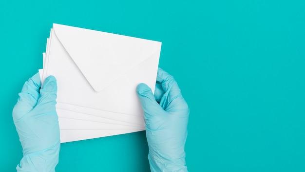 Widok z góry ręki trzymającej koperty medyczne