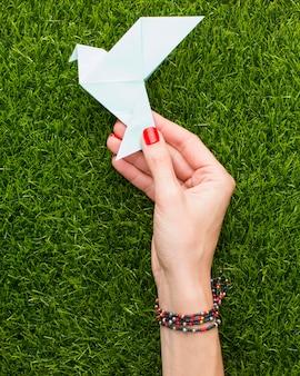 Widok z góry ręki trzymającej papierową gołąbkę na trawie