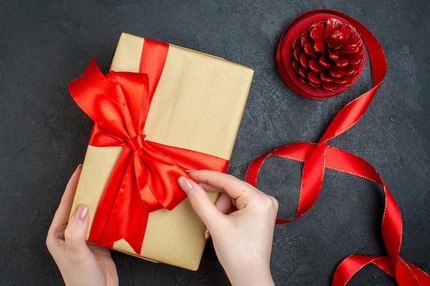 Widok z góry ręki trzymającej piękny prezent i stożek iglasty na ciemnym tle