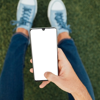 Widok z góry ręki trzymającej smartfon z makiety