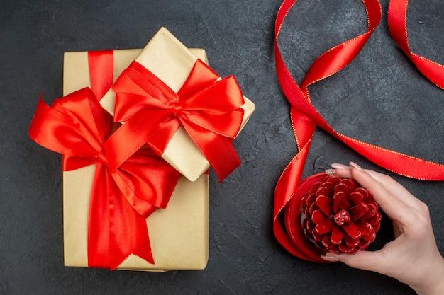Widok z góry ręki trzymającej stożek iglasty i piękny prezent na ciemnym tle