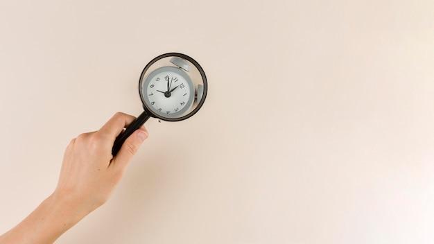 Widok z góry ręki trzymającej szkło powiększające na zegar