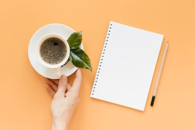 Widok z góry ręki trzymającej talerz z filiżanką kawy