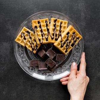 Widok z góry ręki trzymającej talerz z goframi i kawałkami czekolady