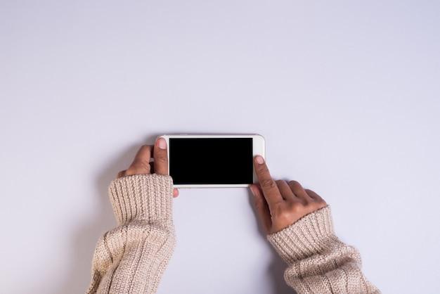 Widok z góry ręki trzymającej telefon komórkowy na białym tle