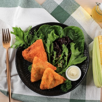 Widok z góry risole warzywne w kształcie trójkąta. cienkie naleśniki nadziewane kukurydzą rogusa, marchewką i zieloną fasolą, podawane na białym talerzu ze świeżymi warzywami i majonezem