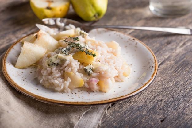 Widok z góry risotto z serem gorgonzola, rodzynkami, migdałami i pieczoną gruszką.