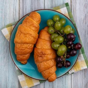 Widok z góry rogalików z winogronami w talerzu na kratę ściereczką na drewnianym tle