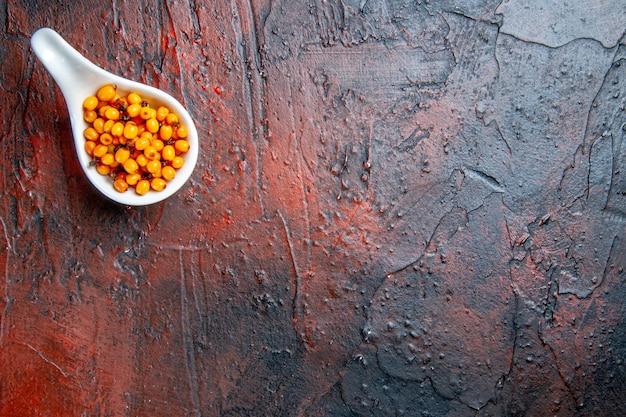 Widok z góry rokitnika w białej misce na ciemnoczerwonym stole
