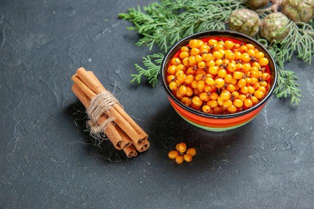 Widok z góry rokitnika w miskę sosna gałąź laski cynamonu na ciemnym stole