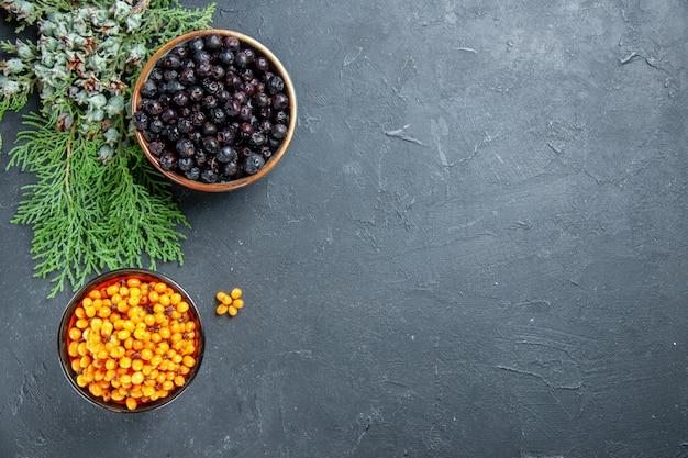 Widok z góry rokitnika zwyczajnego czarnej porzeczki w miseczkach gałąź sosny na ciemnej powierzchni z miejsca na kopię