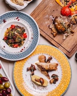 Widok z góry rolada z kurczaka z puree ziemniaczanym, pieczarkami, grillowaną sałatką warzywną i czerwonym mięsem z pieczarkami i sosem na stole
