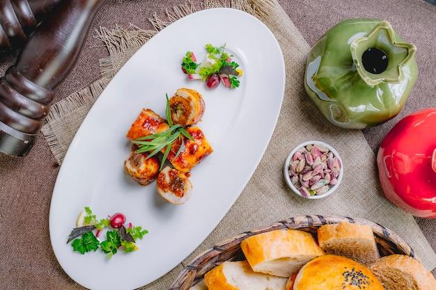 Widok z góry rolada z kurczaka z rzodkiewką zieloną pistacją z derenia i chlebem na stole