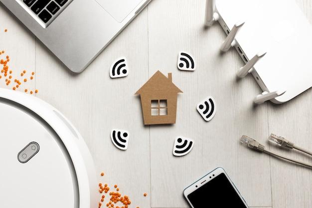 Widok z góry routera wi-fi z figurką domu i urządzeniami sterowanymi bezprzewodowo