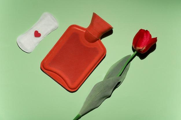 Widok z góry róża, torba na ciepłą wodę i podpaska higieniczna