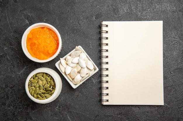 Widok z góry rozgnieciona dynia z nasionami i notatnikiem na szarym tle kolor nasion dojrzałe pomarańczowe zeszyt fotograficzny