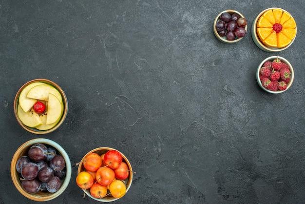 Widok z góry różna kompozycja owocowa świeże, łagodne i pokrojone owoce na ciemnym tle świeże owoce łagodne zdrowie dojrzałe