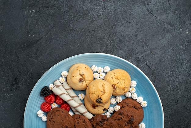 Widok z góry różne ciasteczka słodkie i pyszne ciasteczka wewnątrz na szarej powierzchni