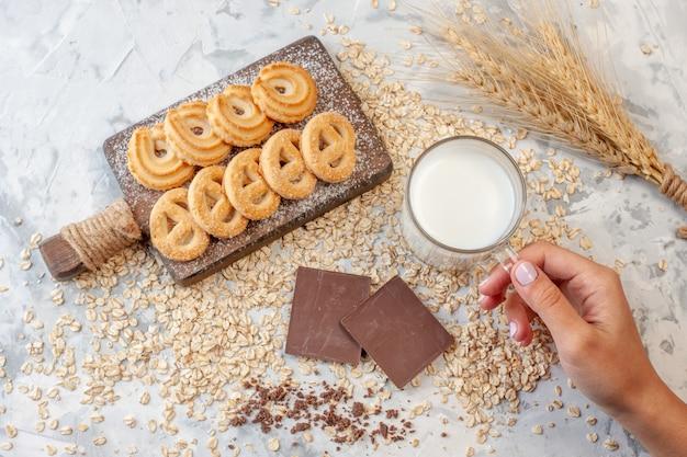 Widok z góry różne ciastka na desce do krojenia czekoladki kolce pszenicy kubek mleka w kobiecie ręcznie rozsypane płatki owsiane na stole