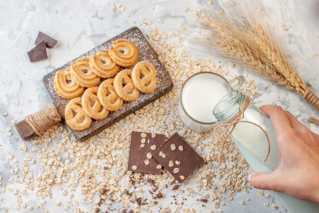Widok z góry różne ciastka na desce do krojenia czekoladki kolce pszeniczne ręcznie wlewanie mleka do szklanki posypane płatki owsiane na szarym tle
