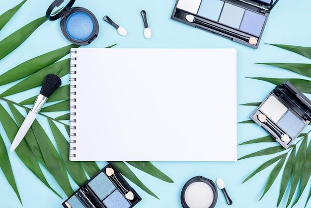 Widok z góry różne kompozycje kosmetyków z pustym notatnikiem