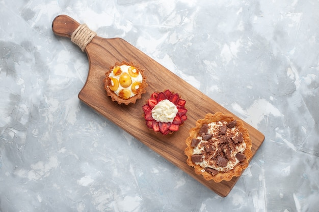 Widok z góry różne kremowe ciasta ciasta owocowe na białym biurku ciasto piec herbatniki słodki cukier owoce