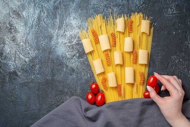 Widok Z Góry Różne Makarony Rigatoni Spirale Spaghetti Pomidor Koktajlowy W Kobiecej Dłoni Fioletowy Szal Na Szarym Tle Wolna Przestrzeń Premium Zdjęcia