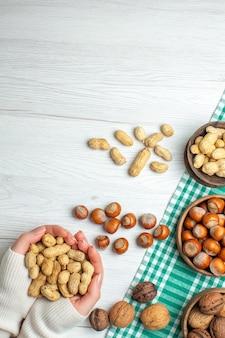 Widok z góry różne orzechy, orzeszki ziemne, orzechy laskowe i orzechy włoskie na białym stole w kobiecej dłoni