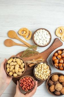 Widok z góry różne orzechy, orzeszki ziemne, orzechy laskowe i orzechy włoskie na białym stole