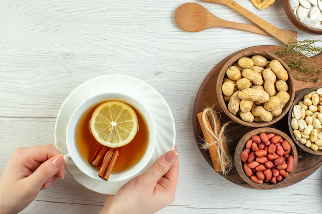 Widok z góry różne orzechy orzeszki ziemne orzechy laskowe i orzechy włoskie z filiżanką herbaty na białym stole