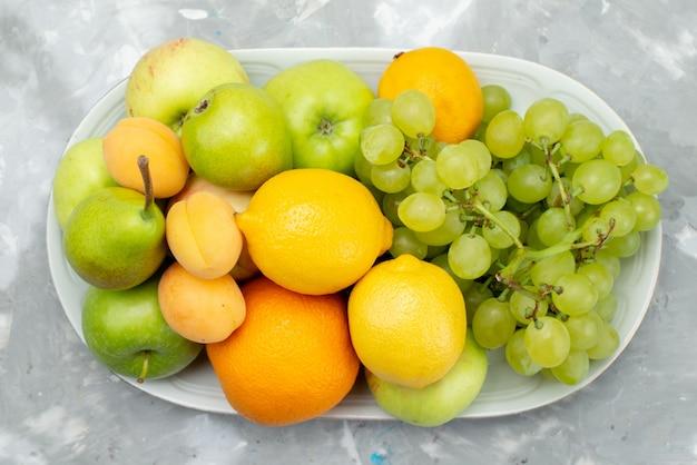 Widok z góry różne owoce, takie jak cytryny, gruszki, jabłka, winogrona i pomarańcze, na białym biurku wewnątrz talerza kolor owoców witamina lato
