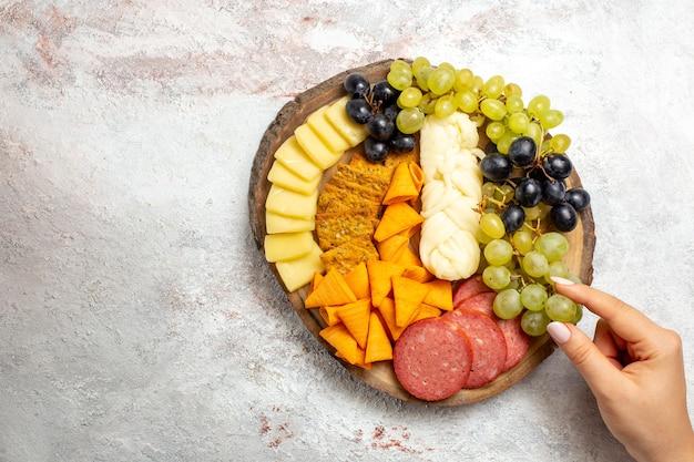 Widok z góry różne przekąski kiełbaski, sery i świeże winogrona na białej przestrzeni