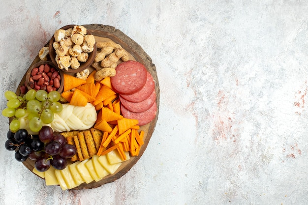 Widok z góry różne przekąski orzechy cips winogrona ser i kiełbaski na białym tle orzechy przekąski posiłek żywności owoce