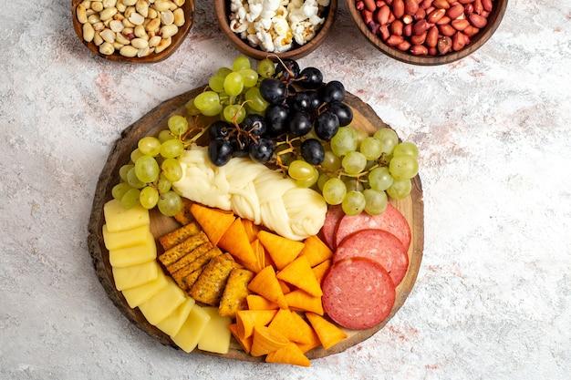 Widok z góry różne przekąski świeże winogrona sera cips z orzechami na białej przestrzeni