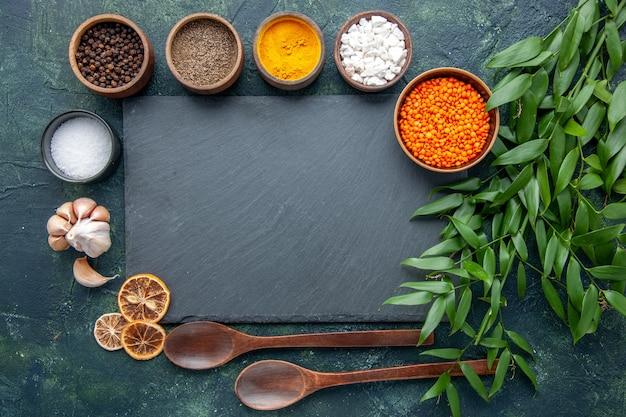 Widok z góry różne przyprawy z czosnkiem i pomarańczową soczewicą na ciemnoniebieskim tle zdjęcie jedzenie pikantna ostra papryka ostra kolorowa zupa z nasion
